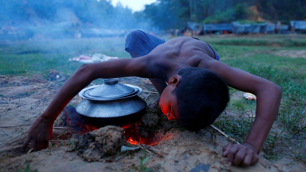 Un refugiado Rohingya enciende fuego para cocinar en su albergue temporal en Bangladesh