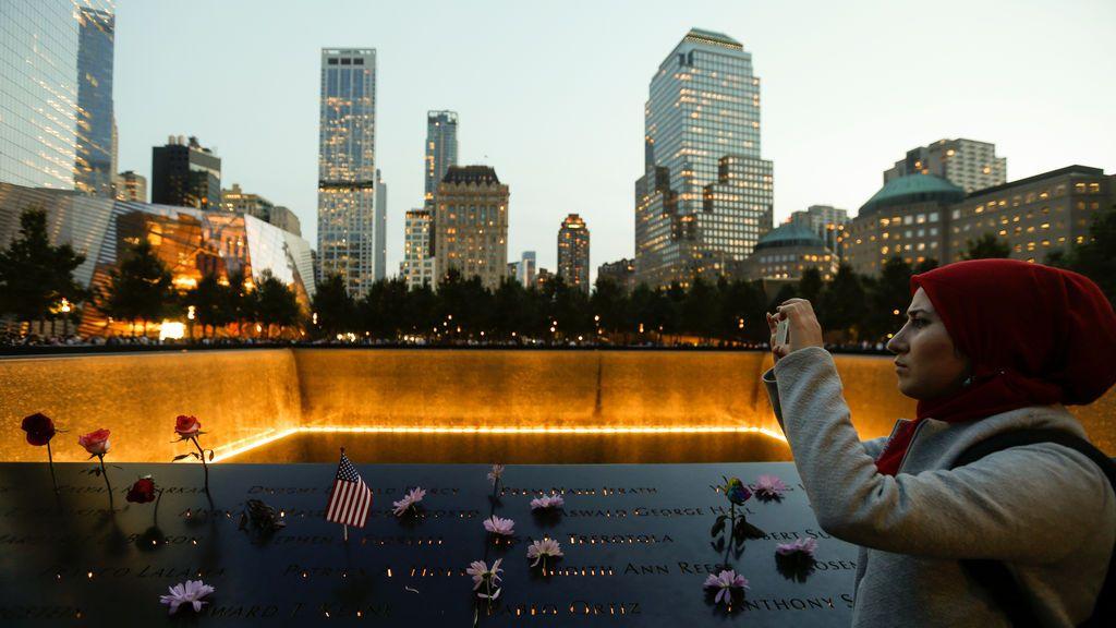 Mujer fotografiando el monumento dedicado a las víctimas del atentado terrorista del 11-S en el 16º aniversario