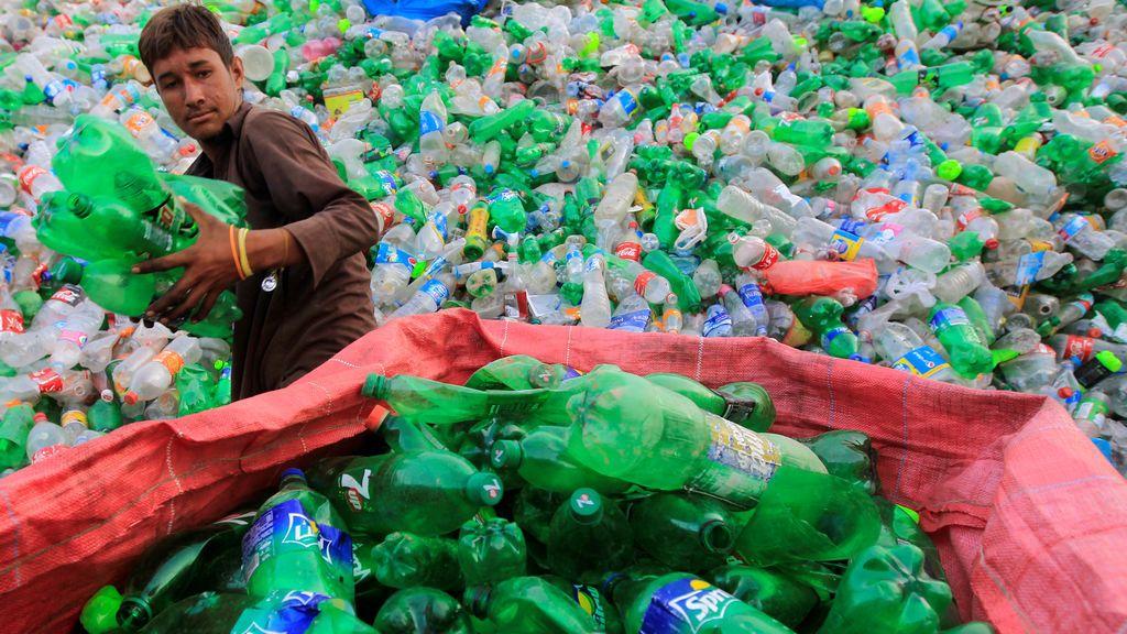 Un trabajador ordena botellas para triturarlas en una planta de reciclaje en Pakistán