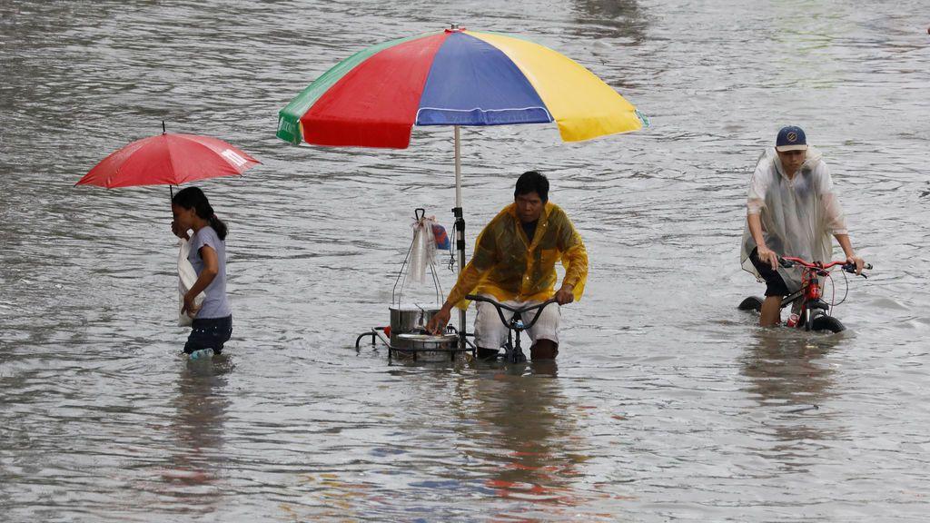 Ciudadanos filipinos circulan por las calles inundadas de Las Pinas, Filipinas