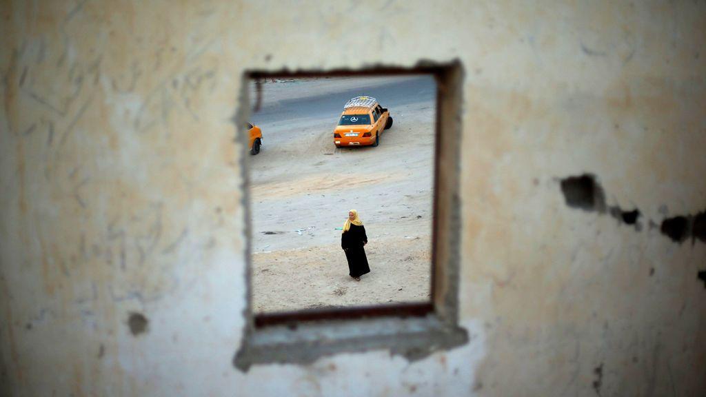 Una mujer palestina es vista a través de una ventana mientras espera el regreso de sus familiares en Gaza