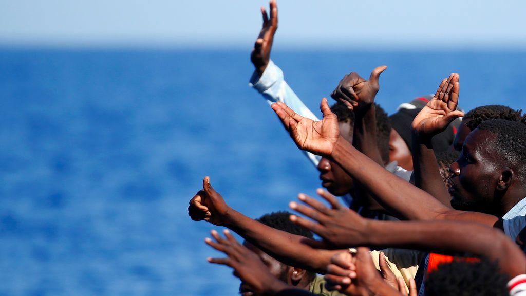 Inmigrantes en una lancha de goma hacen gestos antes de ser rescatados por la organización SOS Méditerráneé