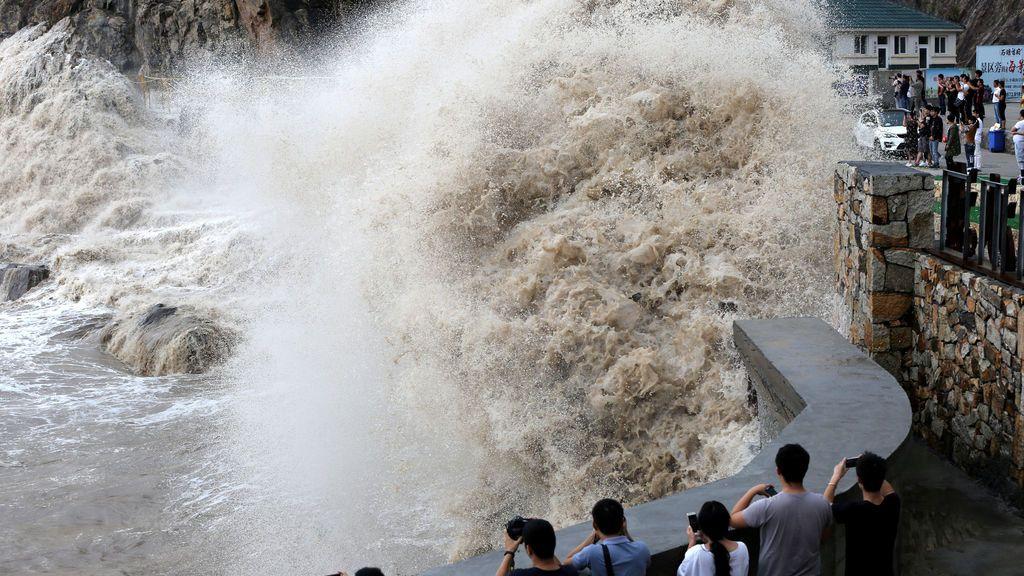 Un grupo de gente observa una gigantesca ola en la costa costa mientras el tifón Talim se acerca a Wenling, China