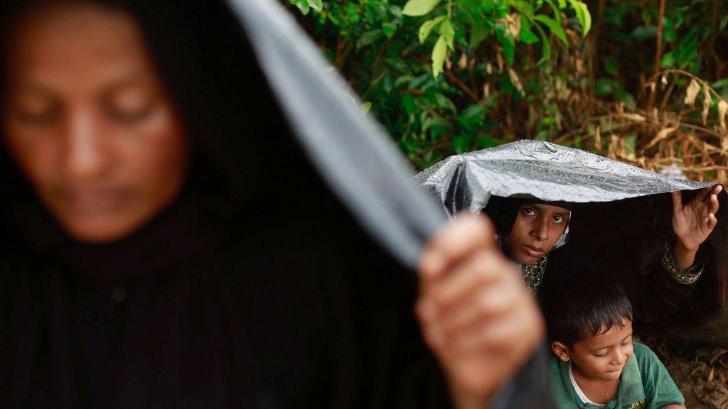 Refugiados rohingya se protegen de la lluvia bajo una lona en un campamento improvisado