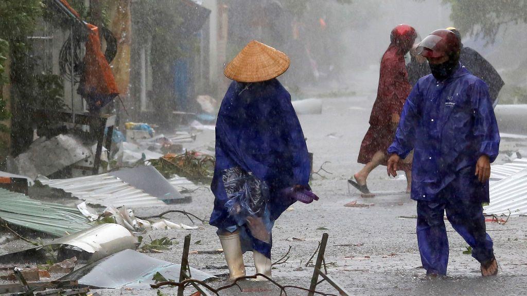 Dos ciudadanos ayudan a limpiar las calles después de la tormenta Doksuri