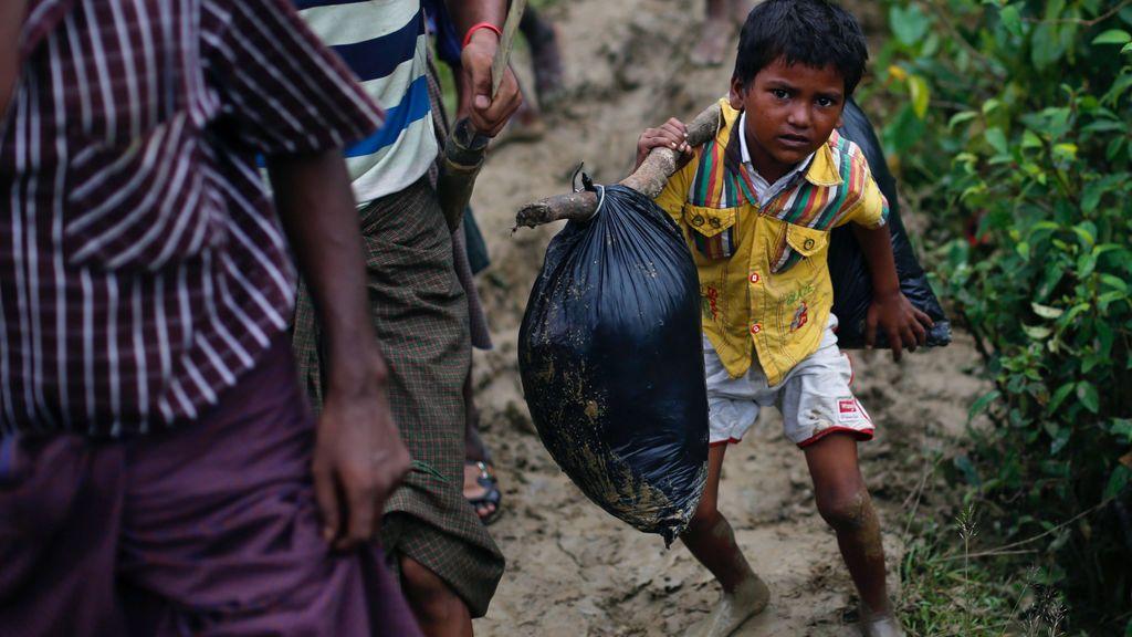 Un niño refugiado Rohingya lleva consigo sus pertenencias a la vez que camina al campo donde va a vivir en Cox's Bazar