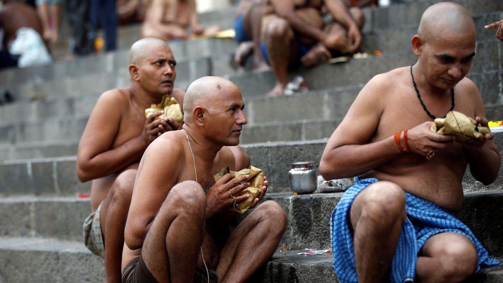 Hindúes realizan rituales como parte de sus oraciones en los pasos del sagrado Tanque Banganga