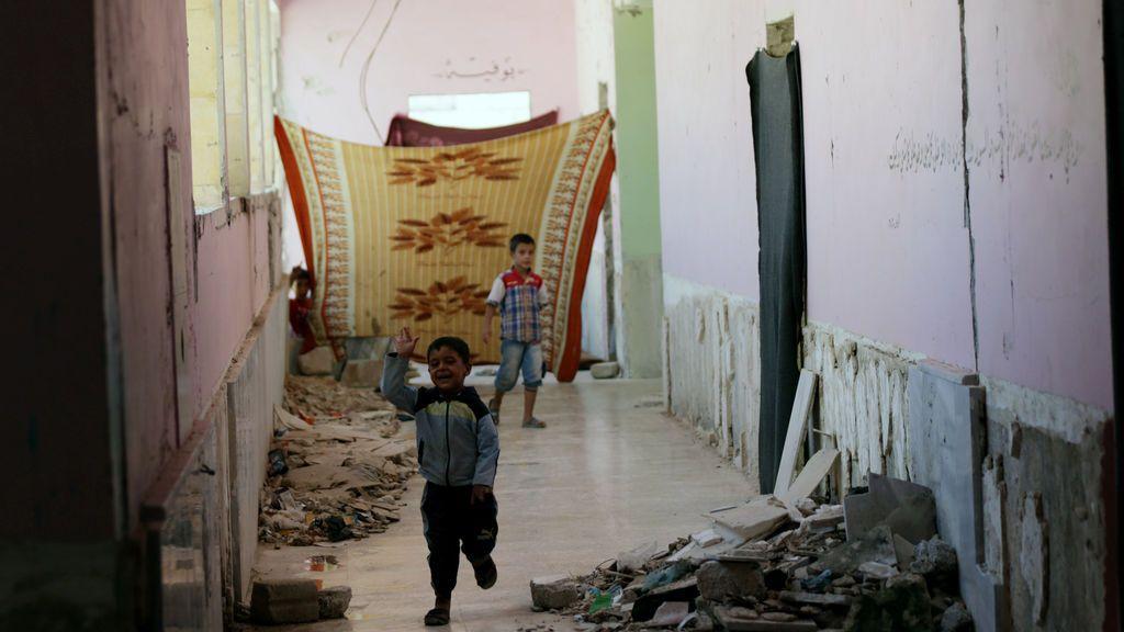 Un niño desplazado interno que huyó de Deir al Zor (Siria) corre en una escuela