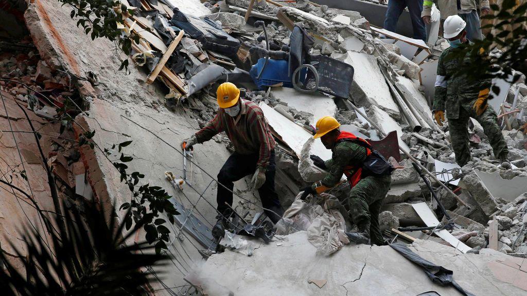 Soldados y voluntarios buscan a las personas atrapadas entre los escombros de un edificio tras el terremoto de México