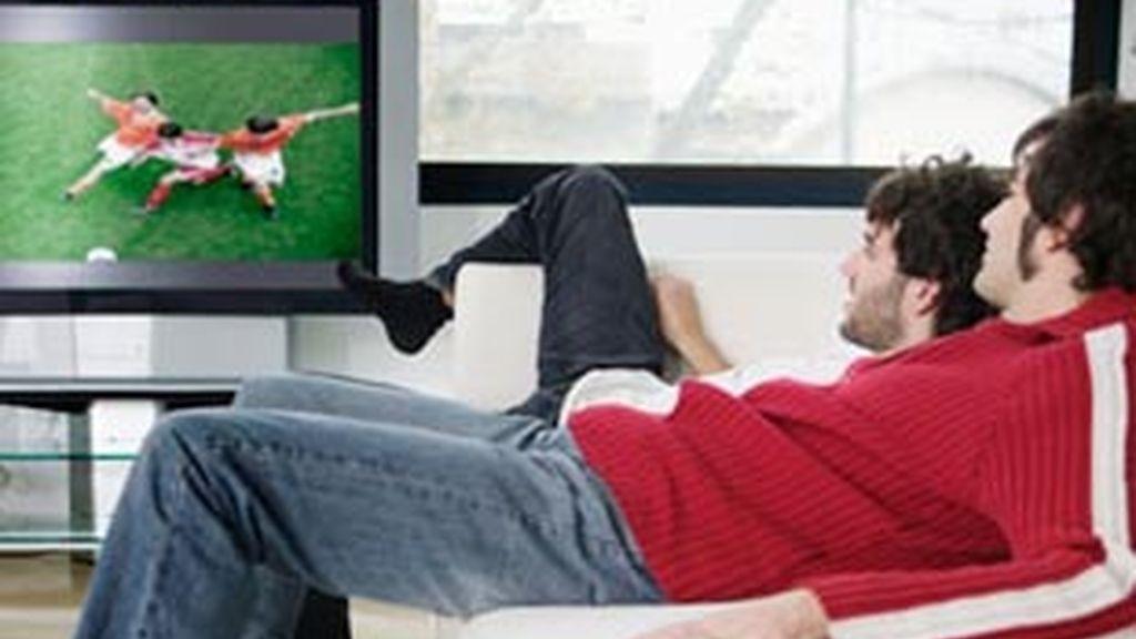 Unos jóvenes ven deportes en televisión.