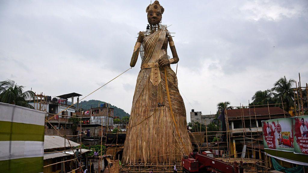 Artistas artesanos instalan una estatua de bambú que representa al ídolo Hindú Durga