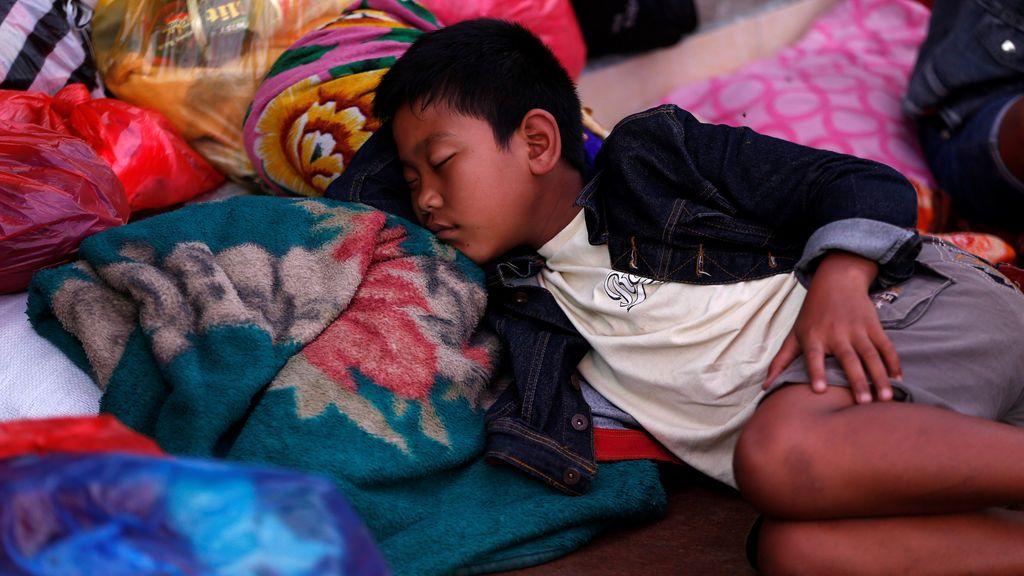 Niño descansa en su refugio tras ser evacuado tras la alerta máxima de erupción de un volcán en Indonesia