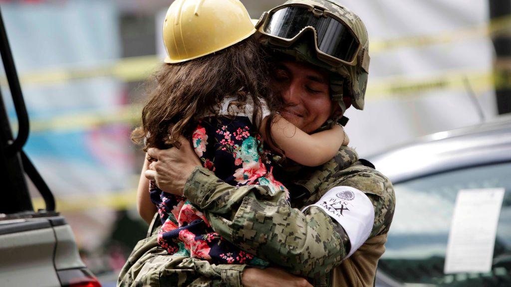 Una niña ofrece abrazos a las personas cerca de un edificio derribado durante el terremoto de México