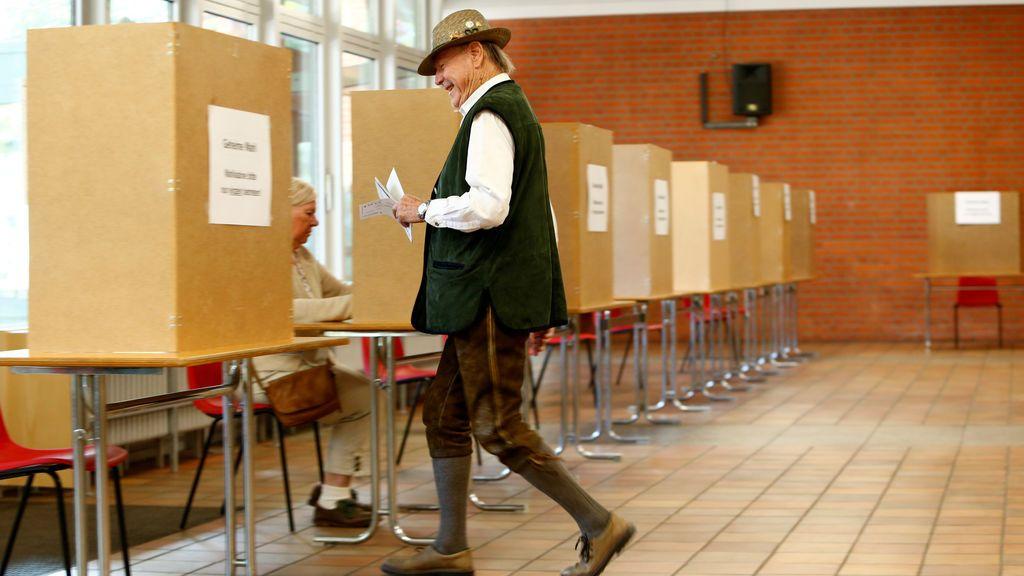Un hombre vestido con el típico traje Bavario se dispone a votar en las elecciones generales de Alemania