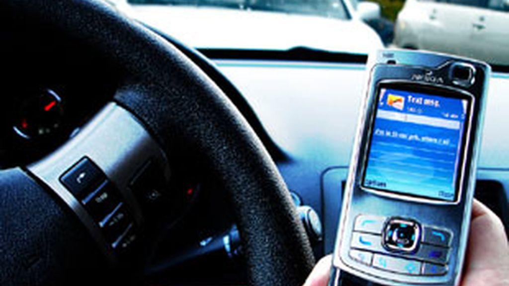 Un conductor escribe un SMS en su móvil.