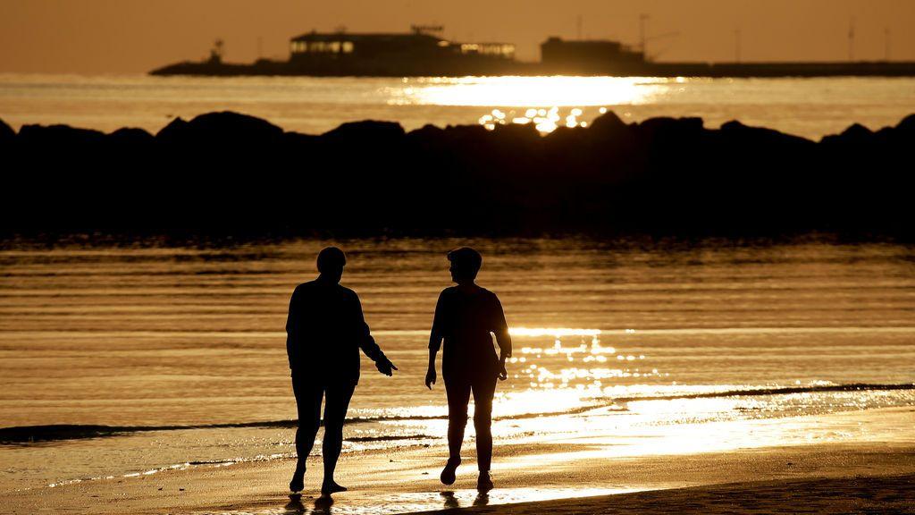 Dos mujeres caminan por la orilla al alba en la playa de Rimini, Italia