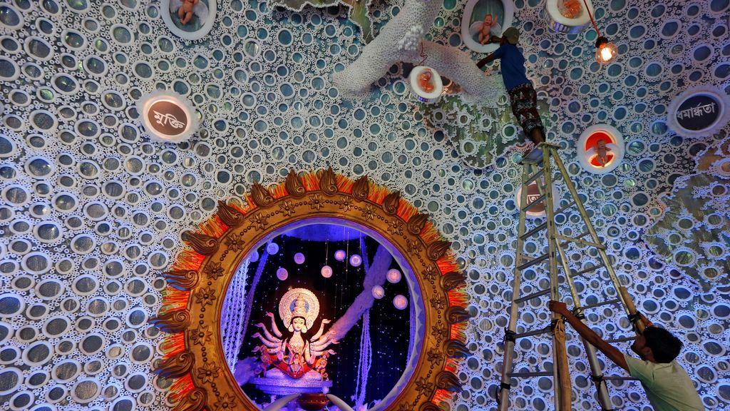 Un electricista examina las luces decorativas de un panal preparado para el festival hindú de Durga, India