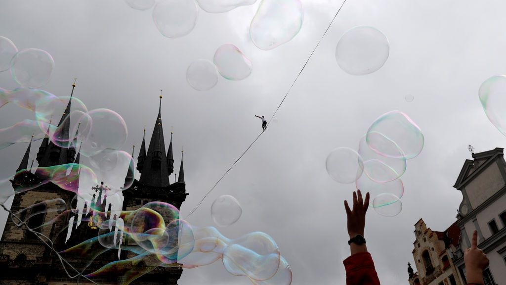 Un hombre se balancea en la cuerda floja mientras unas pompas de jabón flotan en Praga