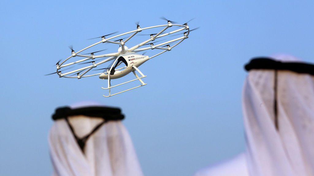 Hombres miran un taxi volador en Dubai