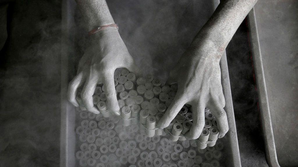 Un trabajador retira rollos de papel después de llenarlos con la mezcla de pólvora