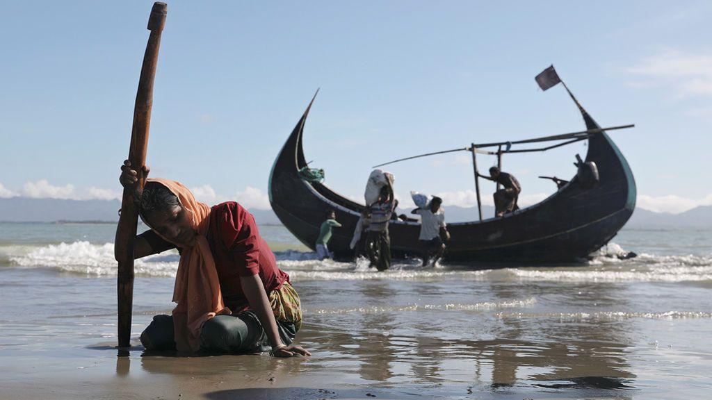 Una mujer cae agotada tras huir de Myanamar