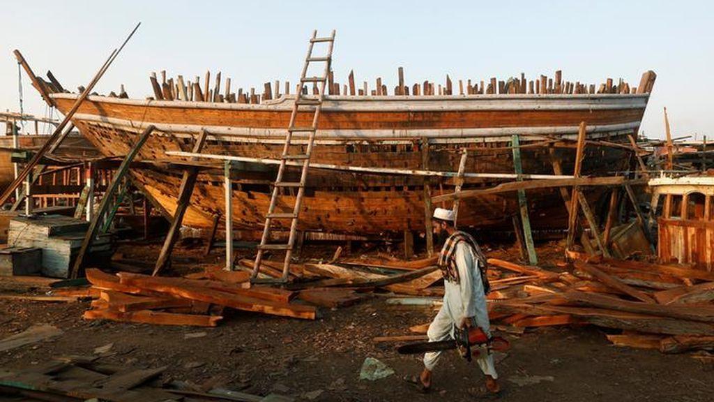 Un carpintero lleva una motosierra mientras camina delante de un barco en construcción