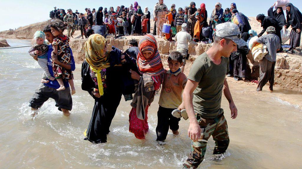 Desplazados cruzan el río para ser transportados a campos de desplazados