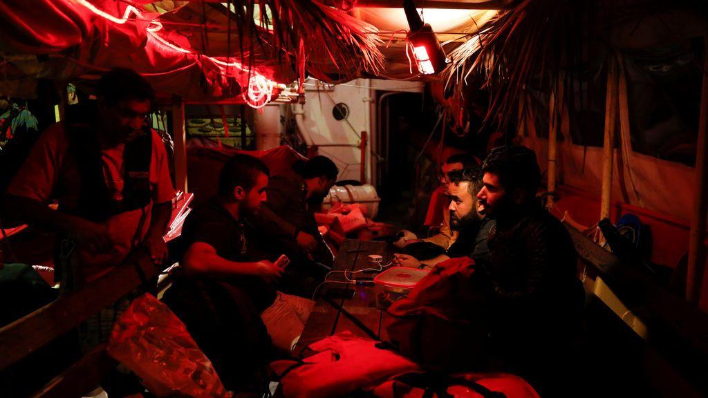 Un tripulante pasa por delante de los inmigrantes libios que acaban de rescatar