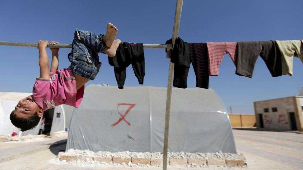 Un niño sirio juega en un campo de desplazados