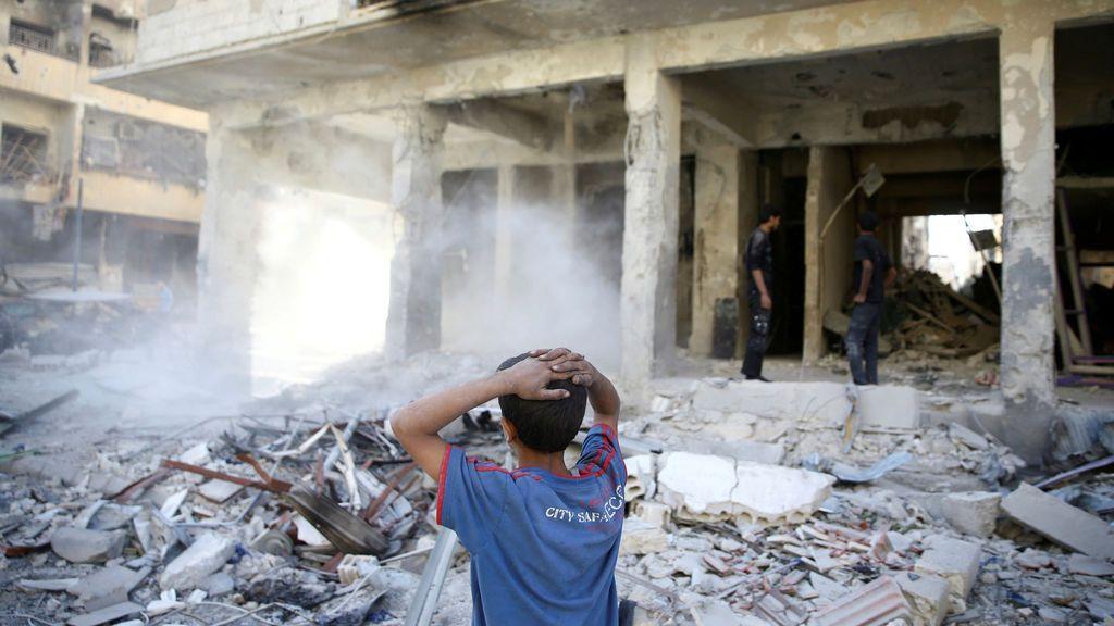 Un niño permanece delante de una posición que acaba de ser bombardeada en Siria