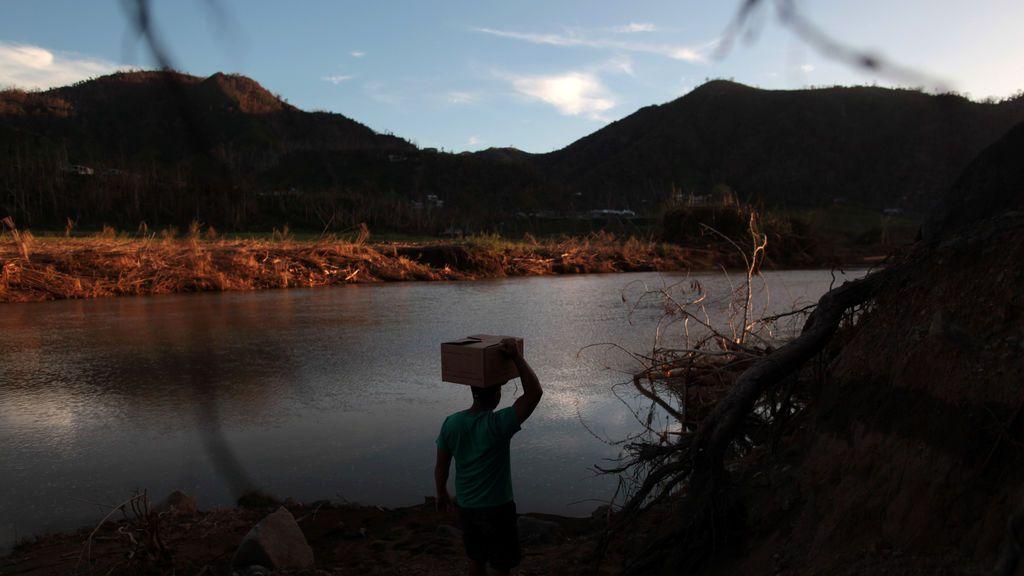 Un residente trasporta una caja con comida por la orilla del río después de que el huracán María destrozara el puente