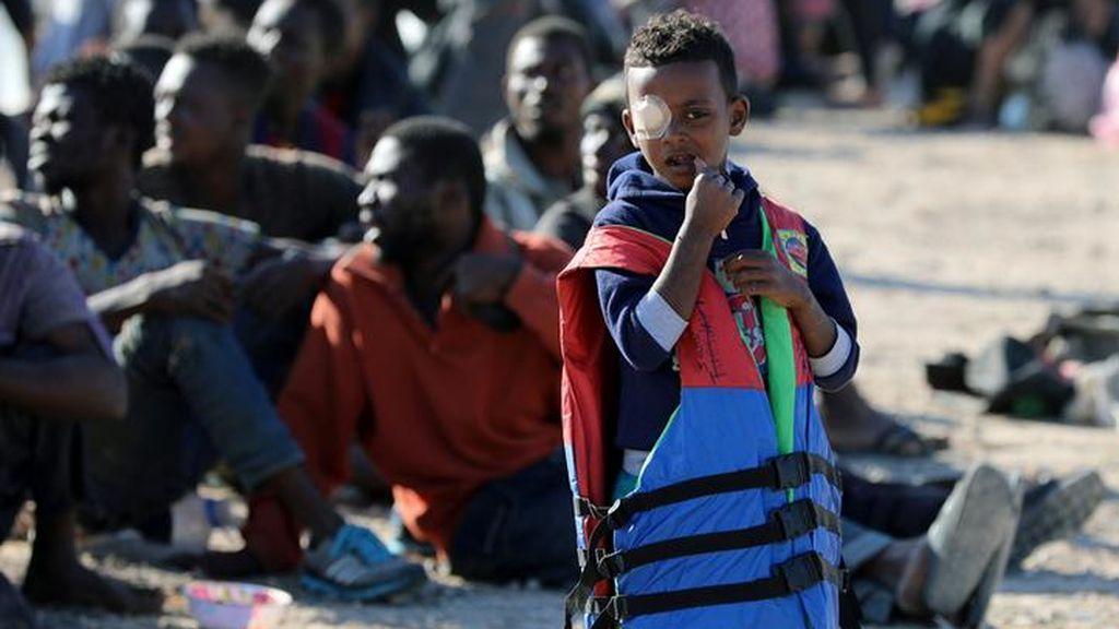 Imigrantes esperan a ser llevados en Libia a un centro de detención