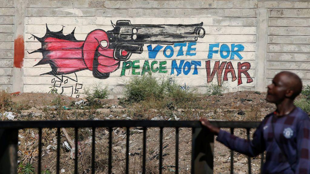 Un hombre pasa por un graffiti cerca de los barrios pobres de Kibera en Nairobi, Kenia