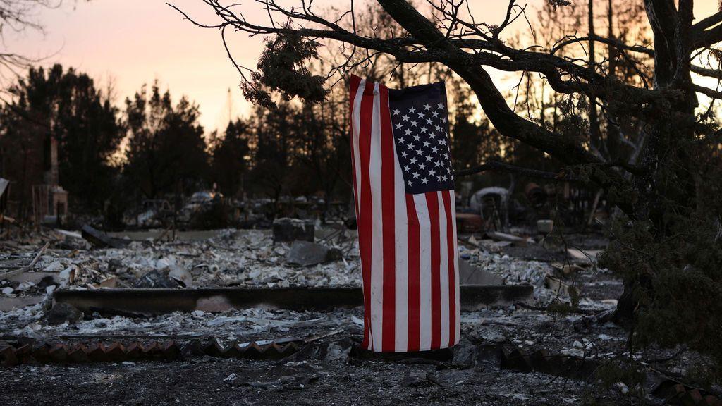 Una bandera americana cuelga de un árbol en un barrio destruido por incendios forestales en Santa Rosa, California, EE.UU.