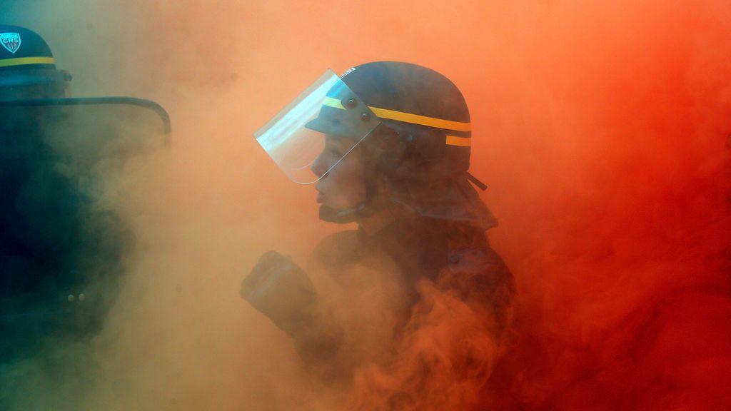 Una agente antidisturbios se enfrenta a trabajadores siderúrgicos franceses durante una manifestación en París
