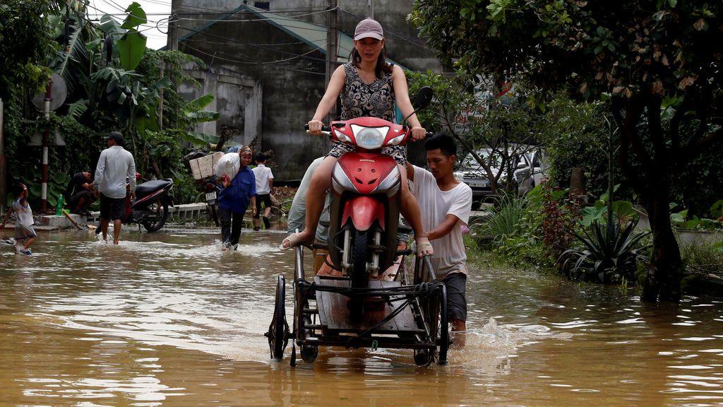 Los hombres evacuan a una mujer a través de un camino inundado después de una depresión tropical en Hanoi, Vietnam