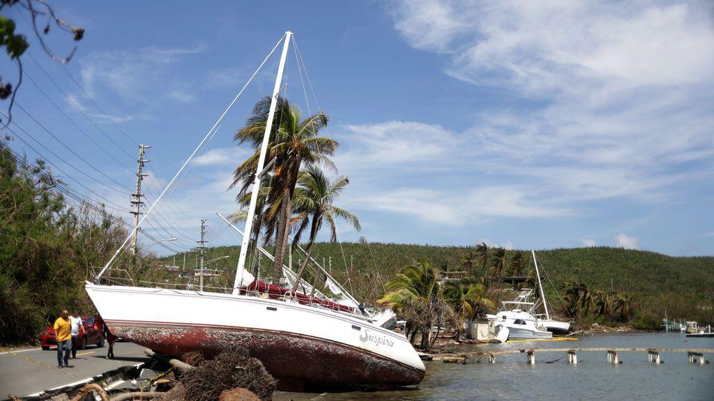 Los hombres pasan por un barco empujado hacia una carretera por los vientos del huracán María en Farjado, Puerto Rico