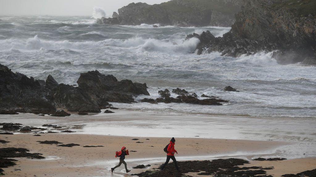 Dos personas caminan por una playa a la que se aproxima Ophelia