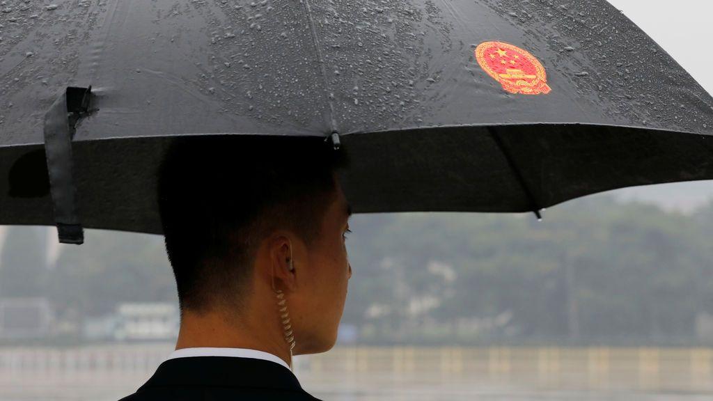 Un soldado de paisano se mantiene bajo la lluvia fuera del Gran Salón del Pueblo