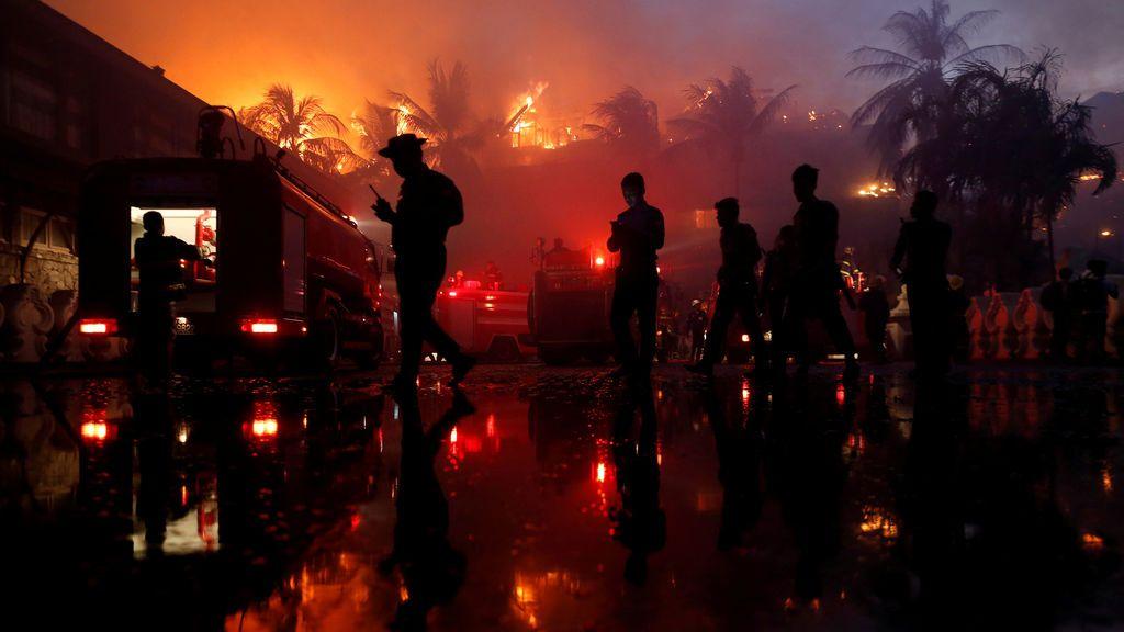 Los oficiales de policía hacen guardia durante un incendio en el hotel Kandawgyi Palace en Yangon, Myanmar