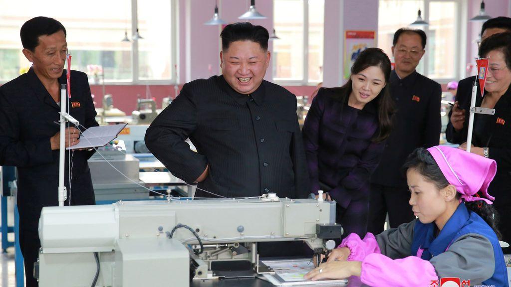 El líder norcoreano Kim Jong-Un, junto con su esposa Ri Sol Ju (centro R), visita Ryuwon Footwear Factory