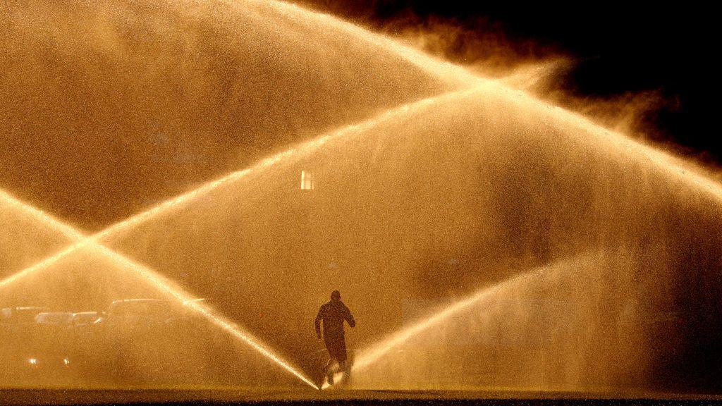 Un corredor pasa entre unos aspersores mientras brilla el sol de la mañana