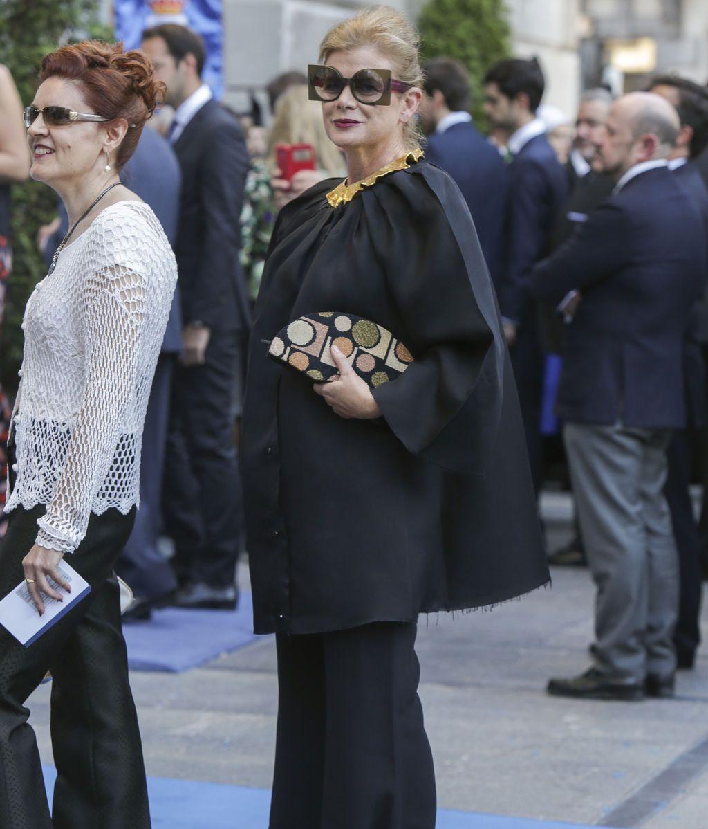 Elena Ochoa de negro con un dos piezas, maxigafas y cartera de mano estampada