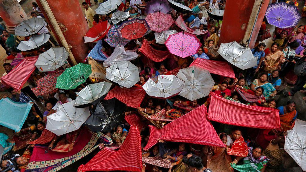 Devotos hindúes sostienen ropa y paraguas para recibir arroz