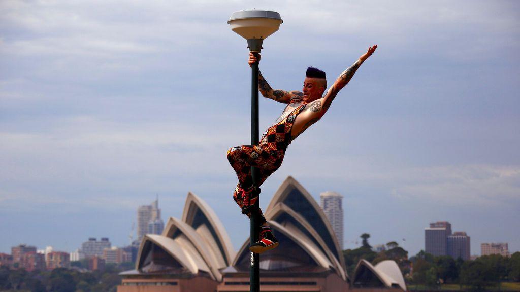 El actor Mitch Jones de Circus Oz después de subir a un poste de luz durante el lanzamiento oficial de la celebración cultural anual The Sydney Festival