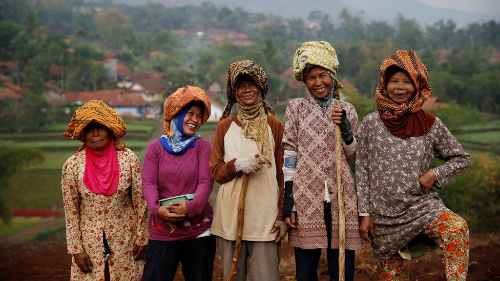 Mujeres posan mientras plantan frijoles en Cikawao, Indonesia