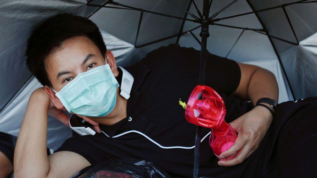Un hombre se enfría con un ventilador portátil mientras los deudos esperan la ceremonia de la Cremación Real del rey Bhumibol Adulyadej de Tailandia en el Gran Palacio en Bangkok, Tailandia