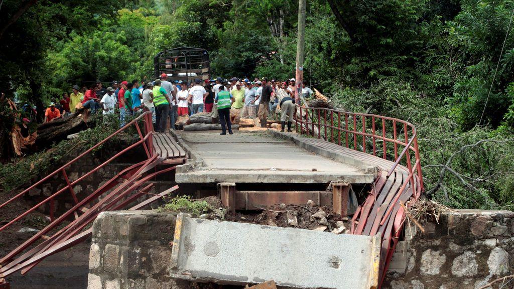 La gente mira un puente dañado por las fuertes lluvias causadas por un área de baja presión que afecta la costa del Pacífico, en Teustepe, Nicaragua