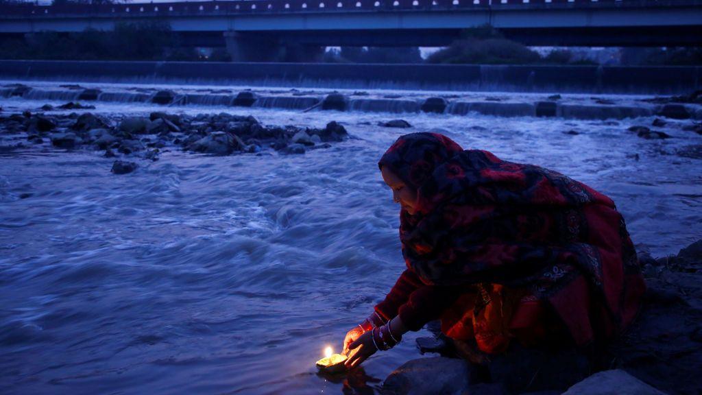 """Un devoto ofrece una lámpara de aceite mientras ofrece una oración al sol naciente durante el festival """"Chhath"""" en el río Bagmati en Katmandú, Nepal"""