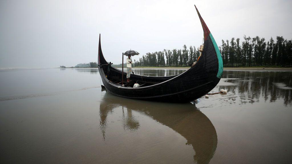 Un hombre sostiene un paraguas mientras está de pie en un bote, que zozobró con un grupo de refugiados rohingya en Bailakhali, cerca de Cox's Bazar, Bangladesh